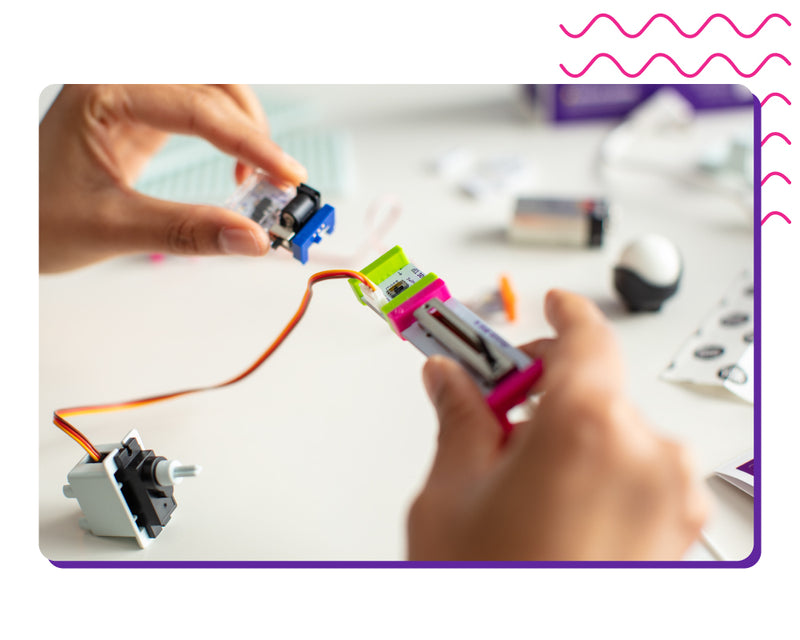 Hands snapping littleBits circuits together.