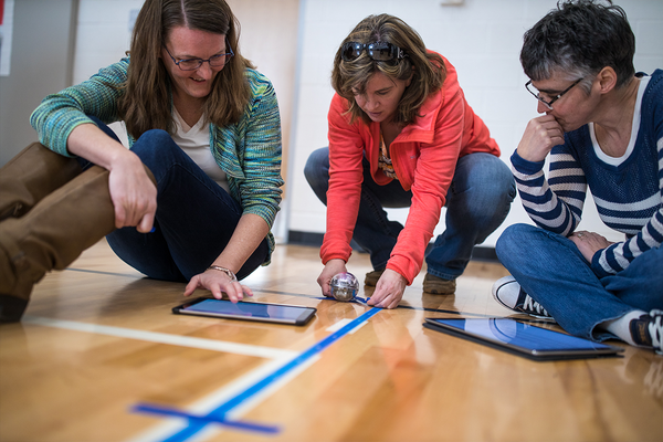 Three educators collaborating on a STEM activity with BOLT robot.