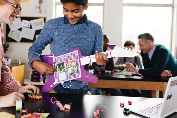 Two boys building a guitar with littleBits circuit STEAM kit.