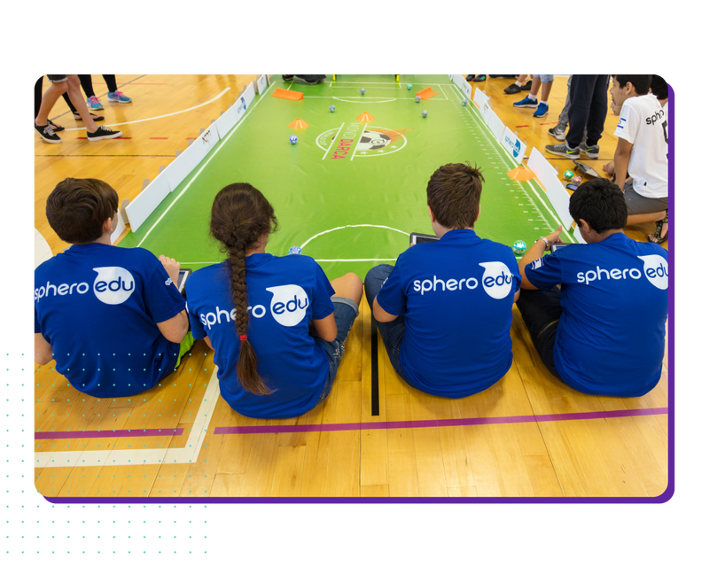 Group of students sitting around a large soccer mat students competing in coding activity.