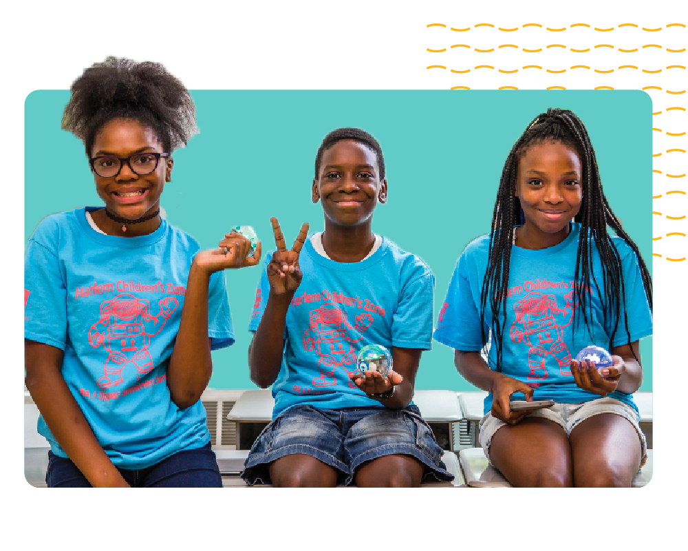 Three young Black students holding up Sphero robots.