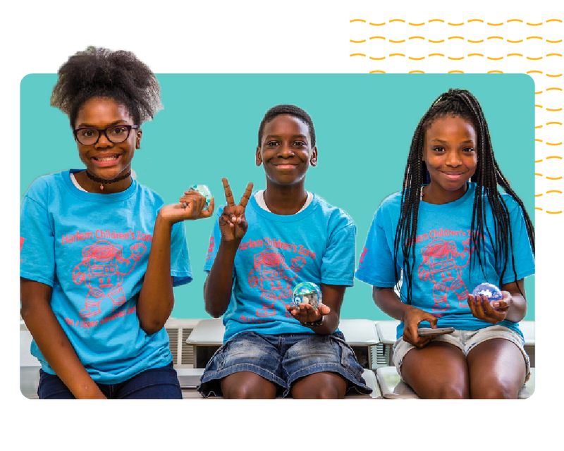 Three African-American students holding STEAM robots.