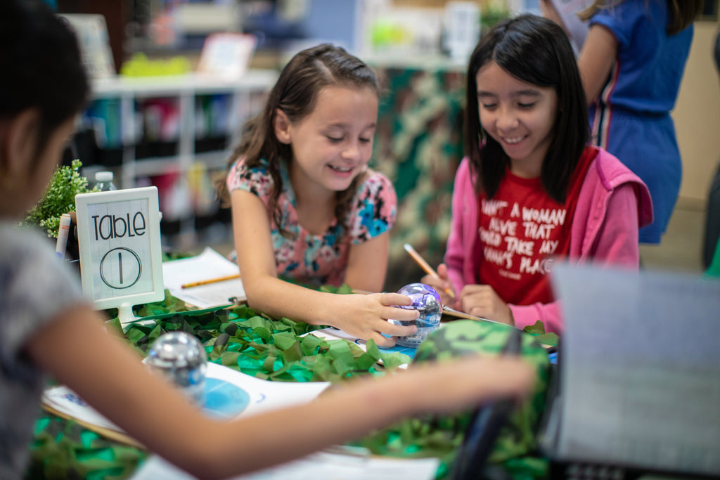 Two girls work side-by-side learning STEM lessons with Sphero BOLT.