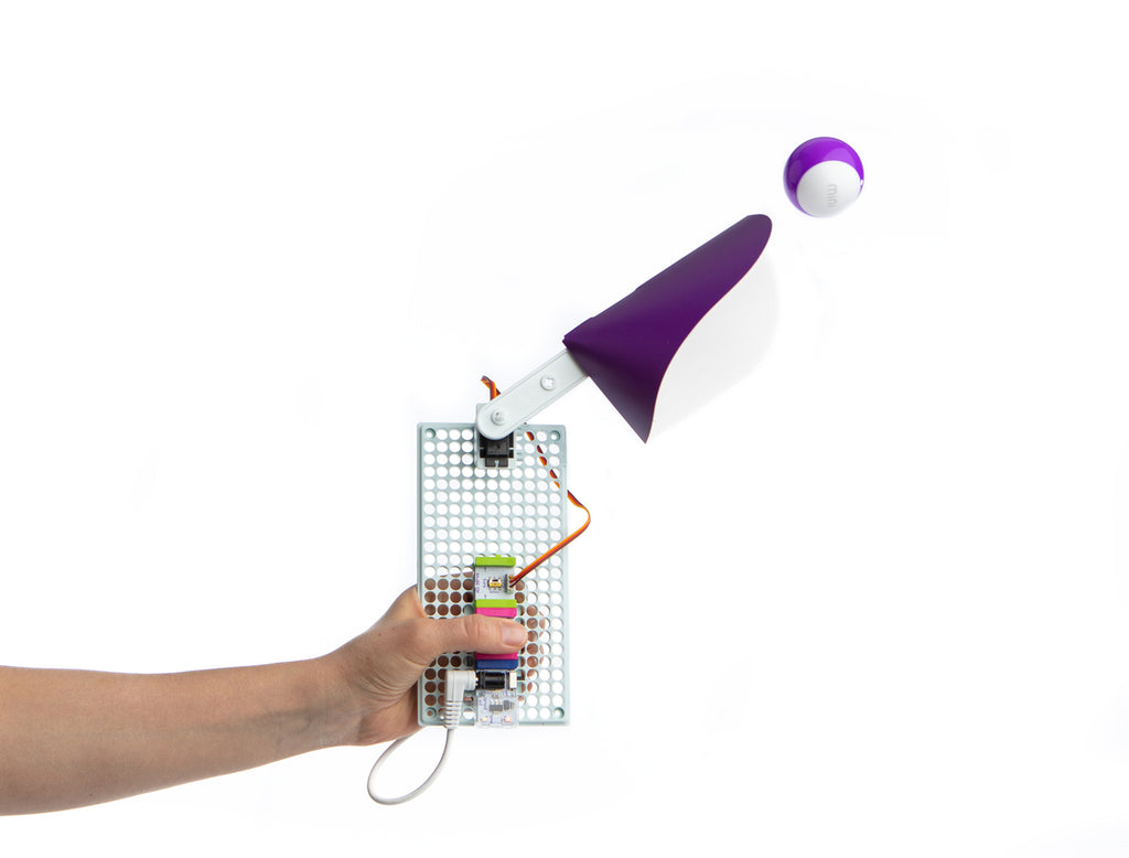 littleBits throwing arm invention in a kid's hand throwing a purple Sphero Mini.