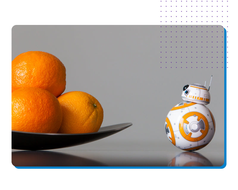 Sphero Star Wars BB-8 rolling up to a bowl of oranges.