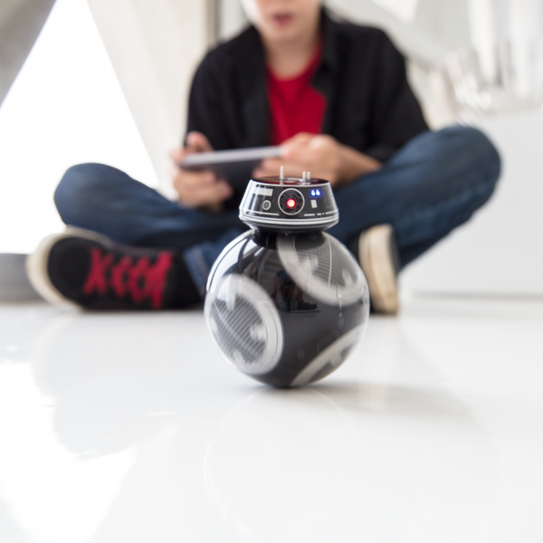 A boy playing with Sphero Star Wars BB-9E.