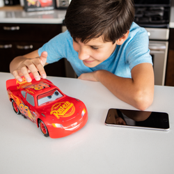 A boy playing with Ultimate Lighting McQueen.