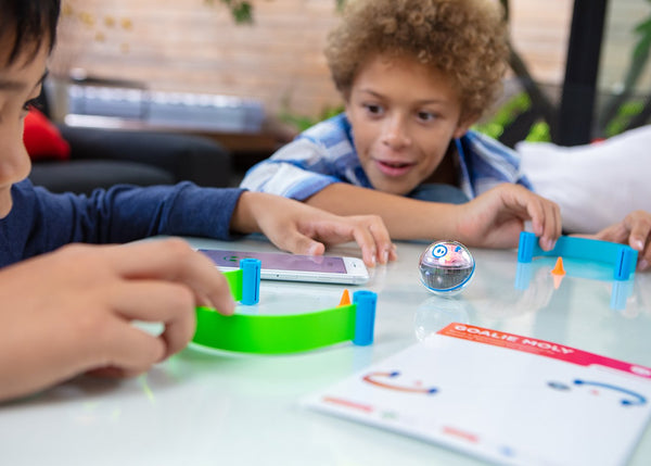 Two boys playing with mini activity kit.