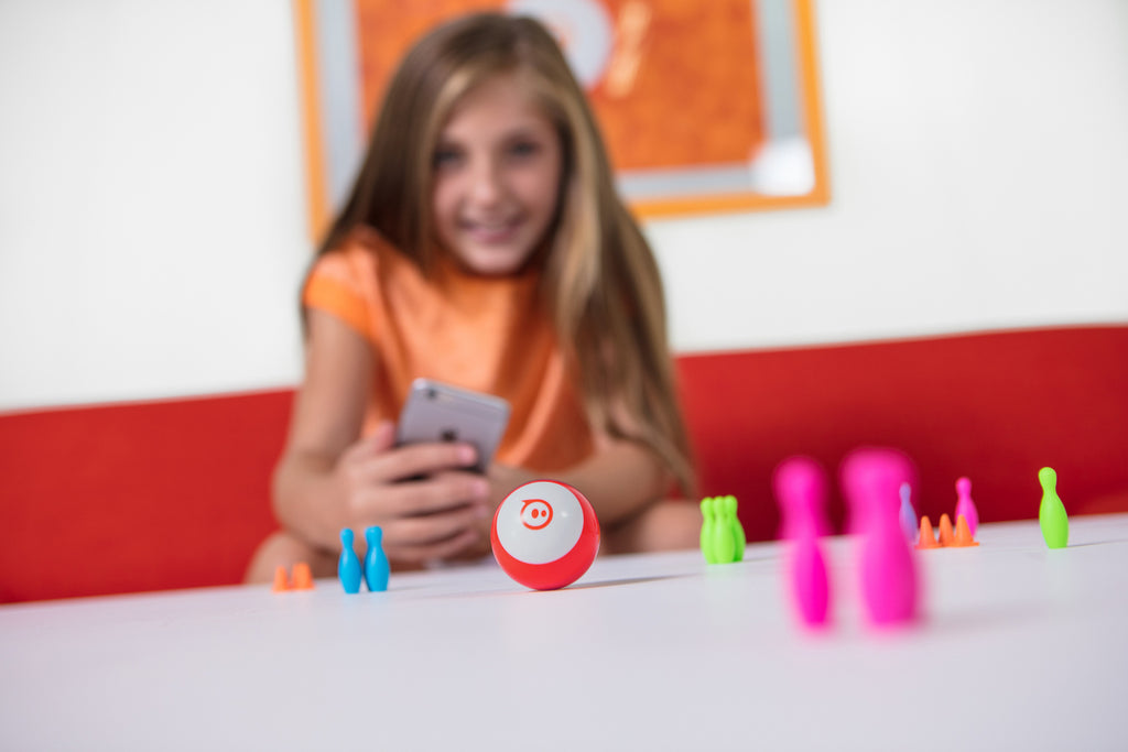 A girl programs her Sphero Mini through bowling pins and cones on a table inside.