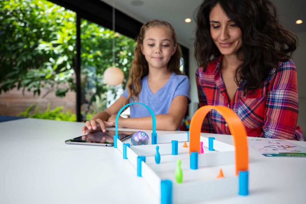 A girl and her mom play with Sphero Mini Activity Kit at their kitchen table.