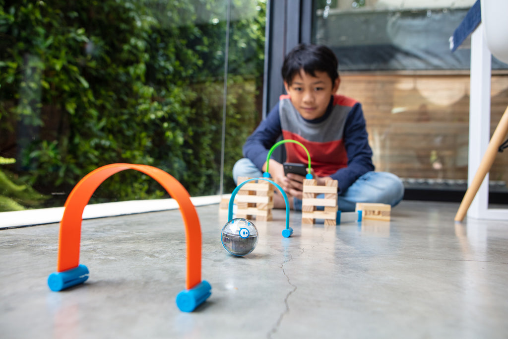 A boy plays with his Sphero Mini Activity Kit on the floor at home.
