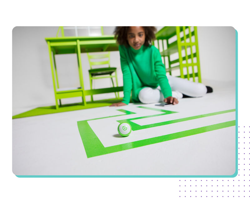 A girl directing a green Sphero Mini through a green maze.