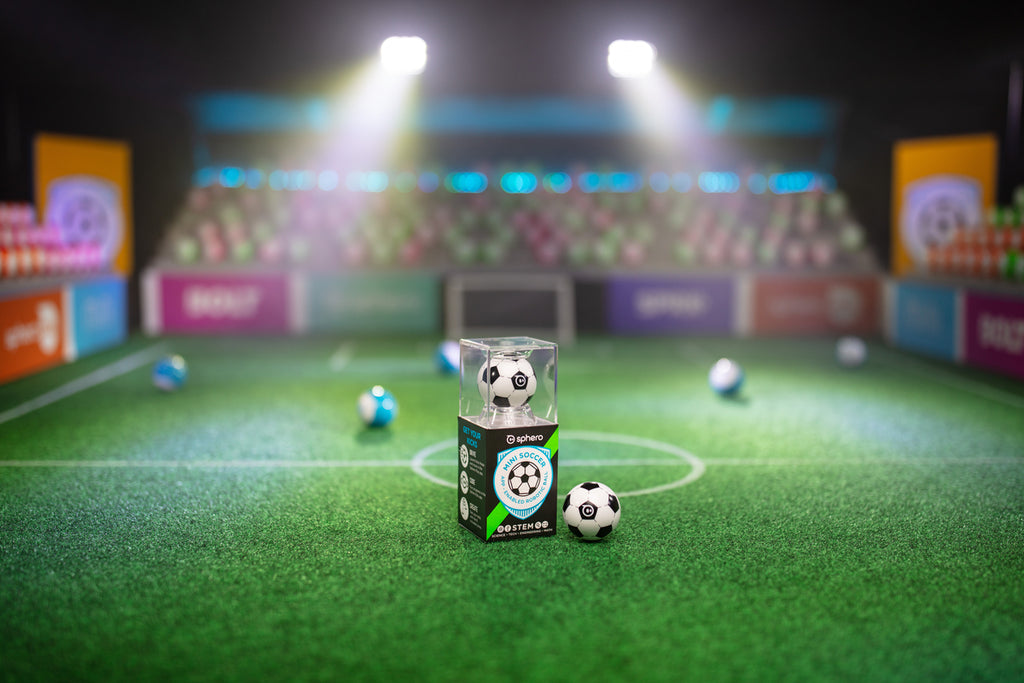 The Sphero Mini Soccer ball on turf under stadium style lights.