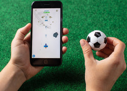 A hand holding a phone and the other hand holding a mini soccer toy robot ball.