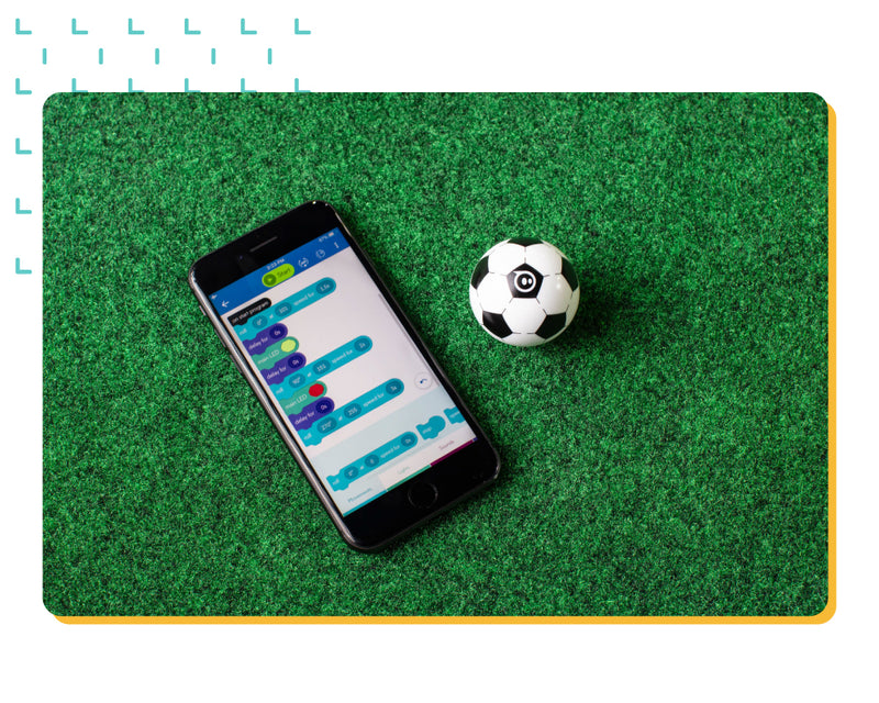 A mobile phone with a block-based based coding application sitting on turf next to a toy soccer robot ball.