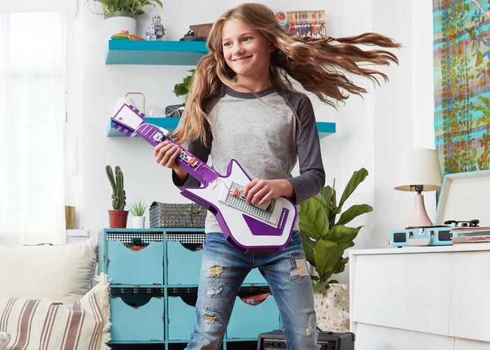 A girl plays on her electronic guitar invention in her bedroom.