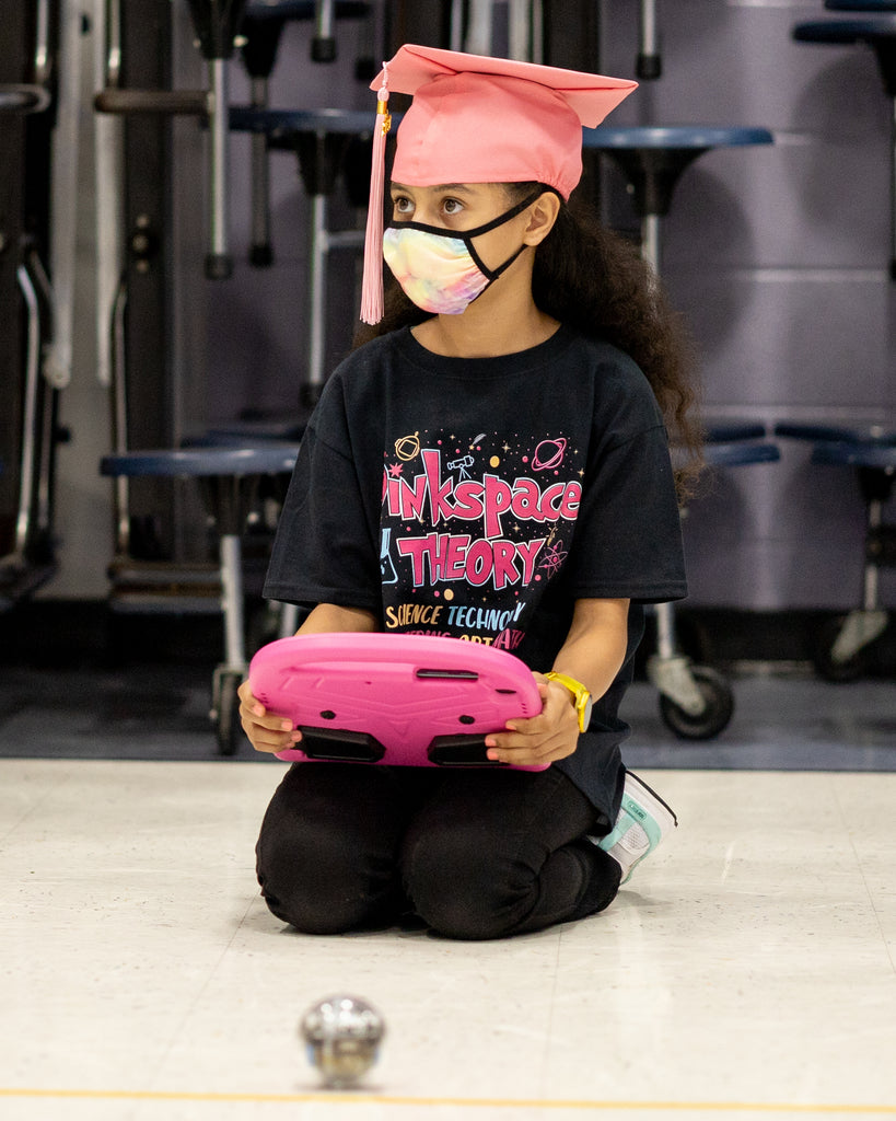 A girl codes a Sphero BOLT as part of the Pink Space Theory STEM program for girls.