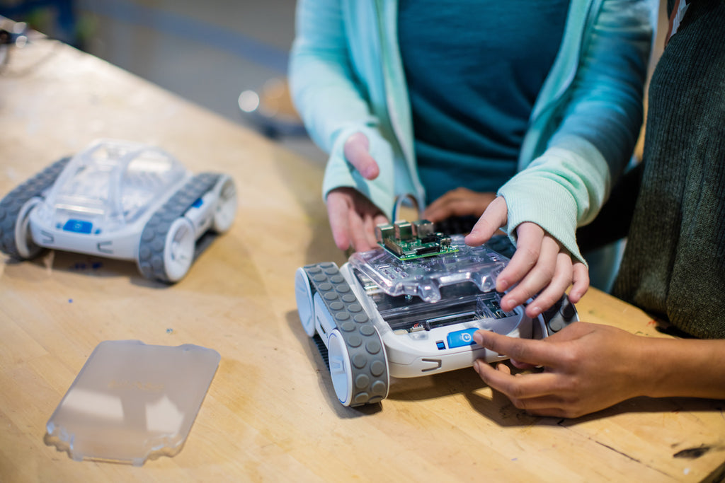 Two girls hands are shown building an invention on top of Sphero RVR.