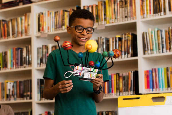 Middle school boy in library holding a model of the solar system that is connected to littleBits