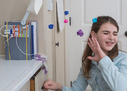 Girl being hit with projectiles from littleBits room defender invention.
