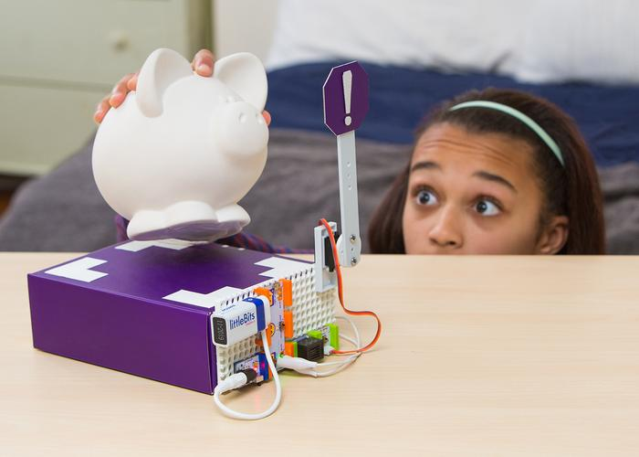 A girl tries to move a piggy bank from a room that has been set up like an alarm with littleBits.