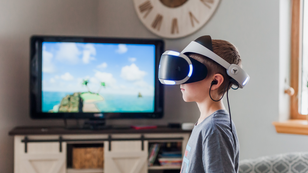 A boy wears a virtual reality headset in the living room in front of a TV.