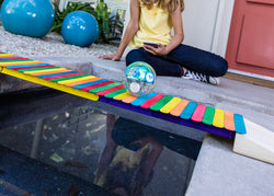 A toy robot ball resting on a colorful bridge built from sticks.