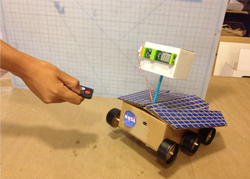 Person pointing a remote at a DIY space rover.