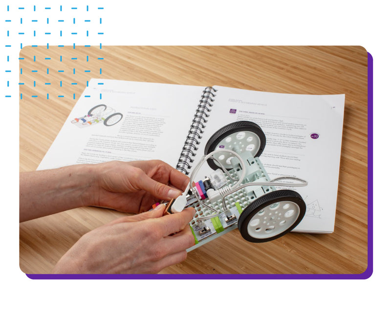 Person building littleBits vehicle using Teacher's Guide book.