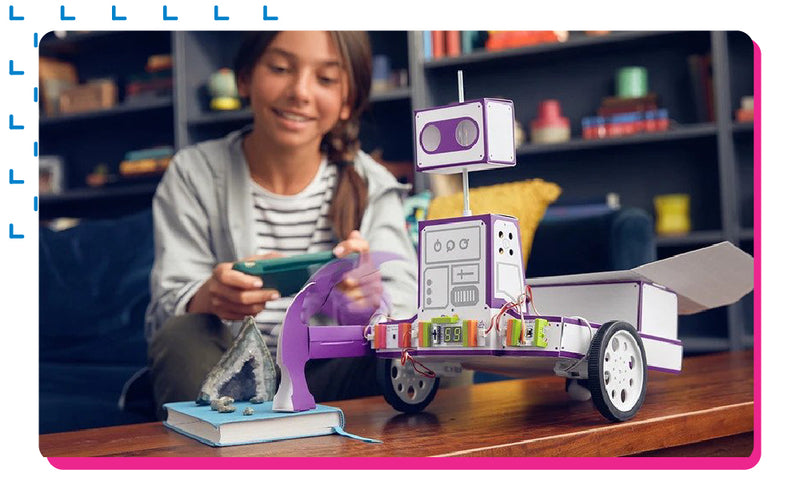 Girl having fun playing with littleBits Space Rover invention.