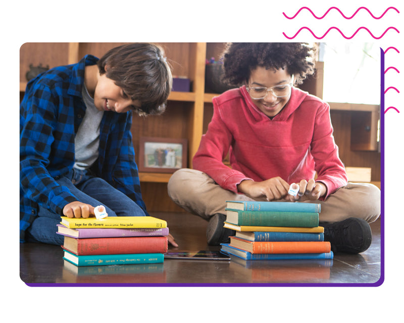 Two kids playing with Specdrums rings on colored books.