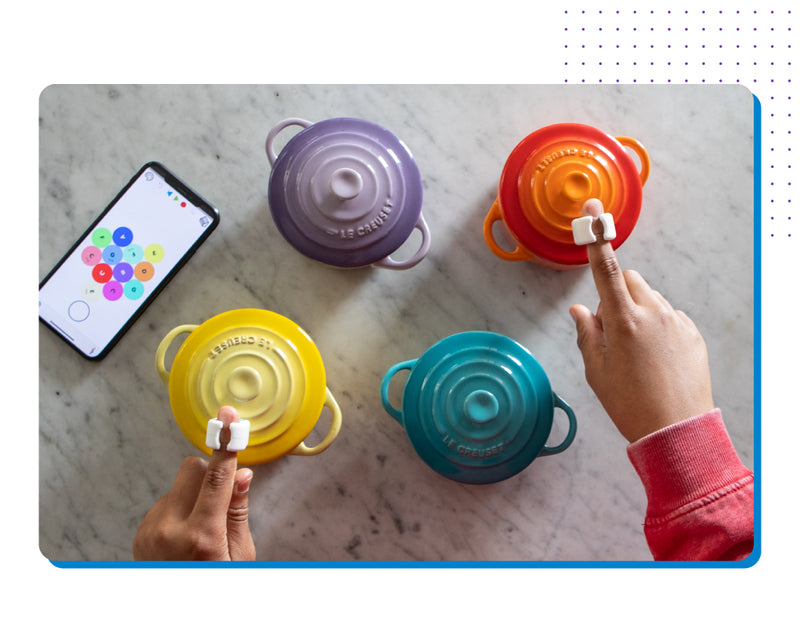 Hands tapping Specdrums rings on colored pots with the Specdrums Edu app.