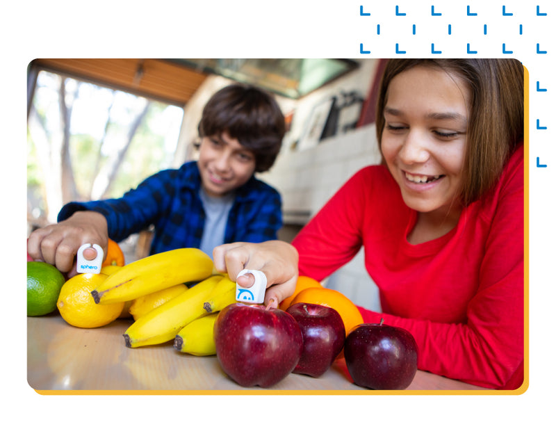 Girl and boy having fun tapping Specdrums rings on fruit.