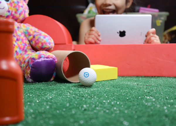 A hand driving a toy robot soccer ball using block-based coding through the Sphero Edu app.