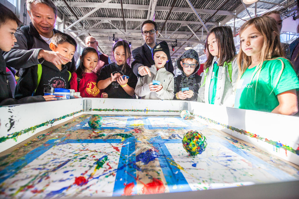 Kids stand around a table while a Sphero robot paints on paper.