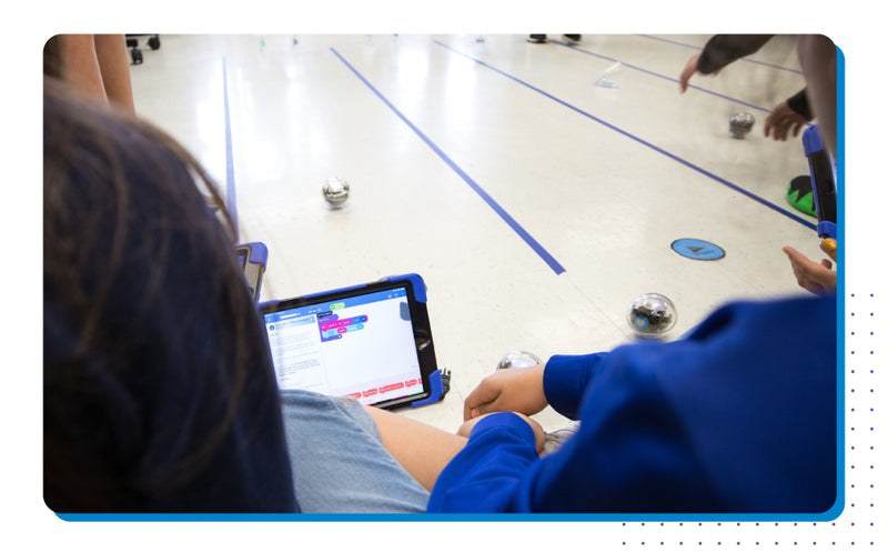 Student playing with Sphero BOLT in classroom.