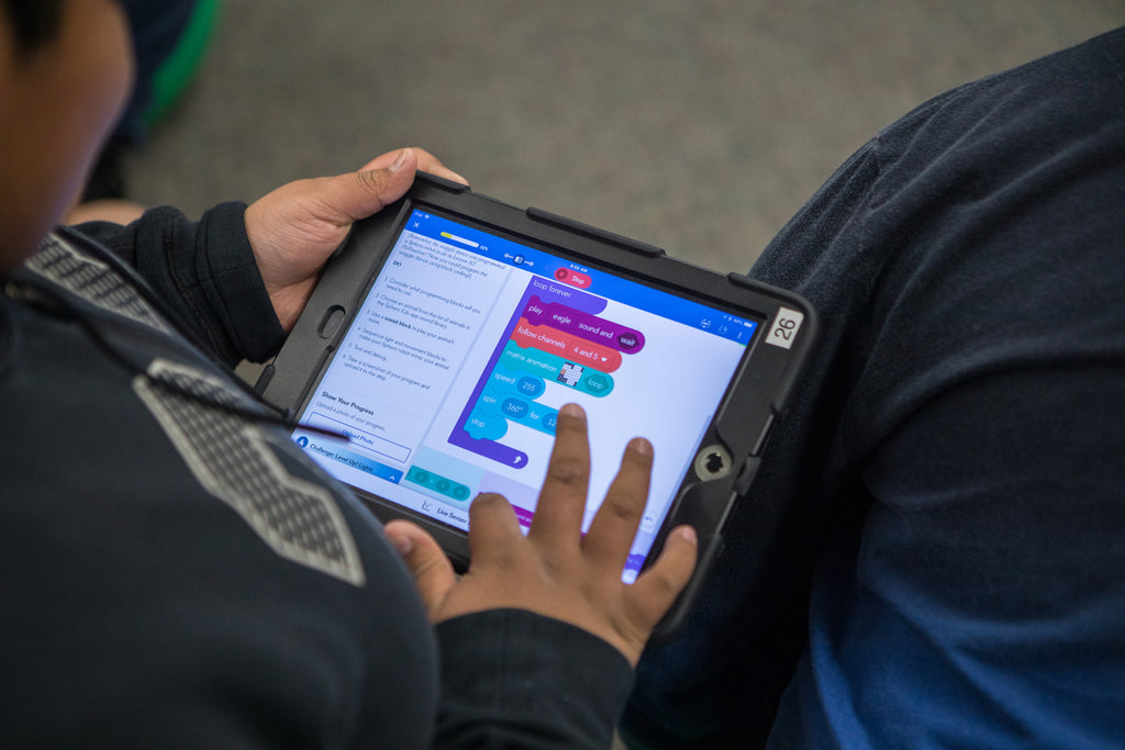 A boy sits on the floor coding on a tablet in the Sphero Edu app.