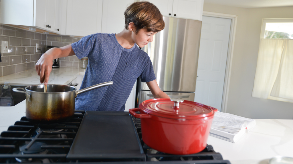 A teenage boy references a cookbook in the kitchen. Following a recipe is a good example of real-world algorithms in action.