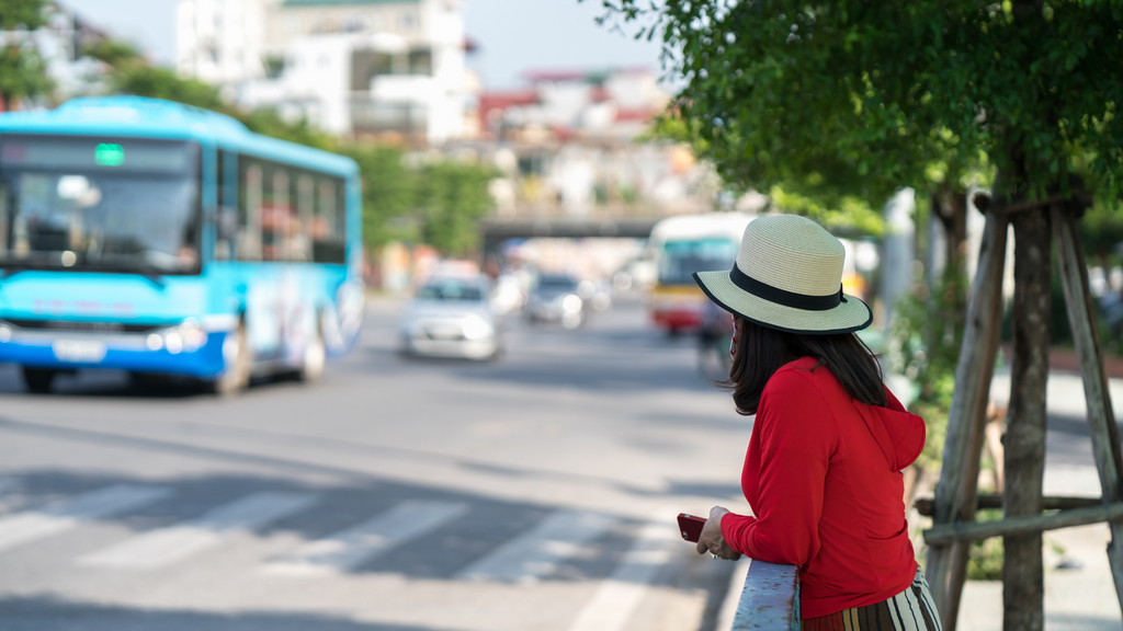 A woman waits for a bus. The schedule busses follow to make on-time arrivals and departures is an example of a real-world algorithm.