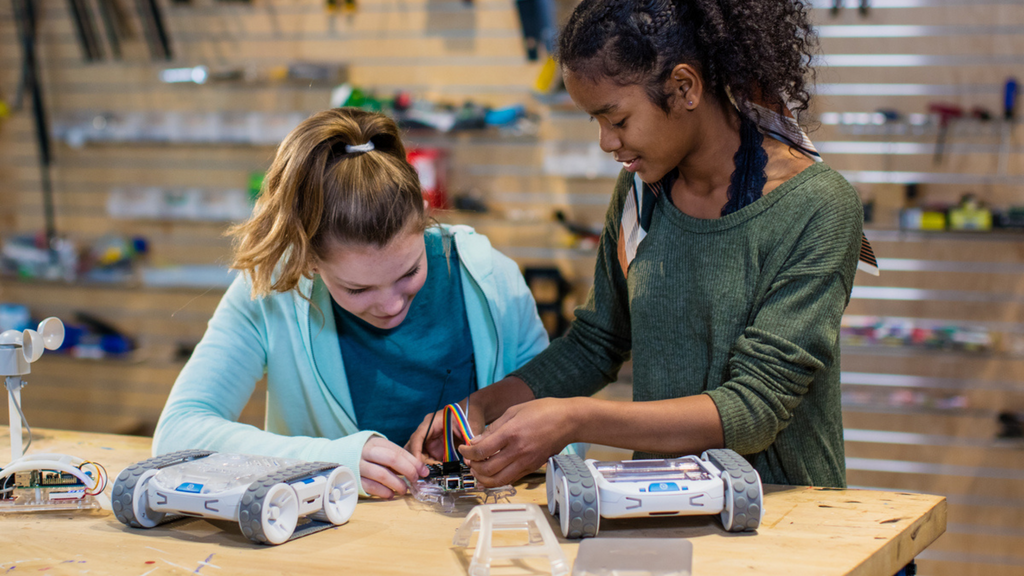 Two high school girls work on a Sphero robot as a back to school activity.