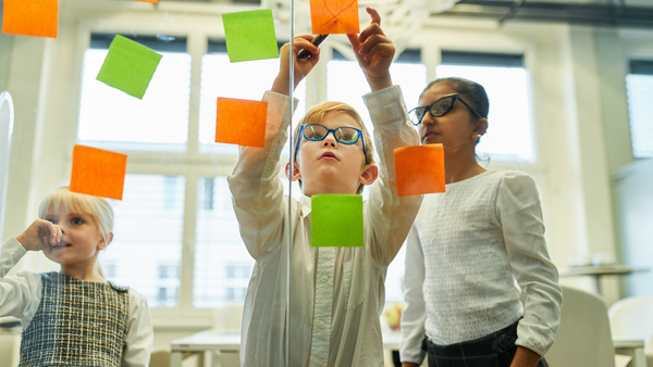 Three kids put sticky notes on a window in a classroom during a brainstorm session.