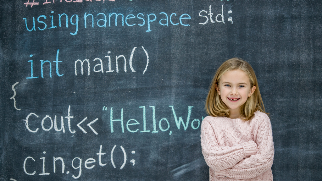 A girl stands in front of a chalkboard with code written on it.