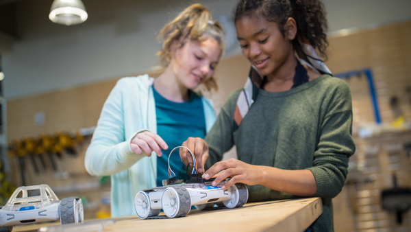Two student girls building on top of Sphero Rover.