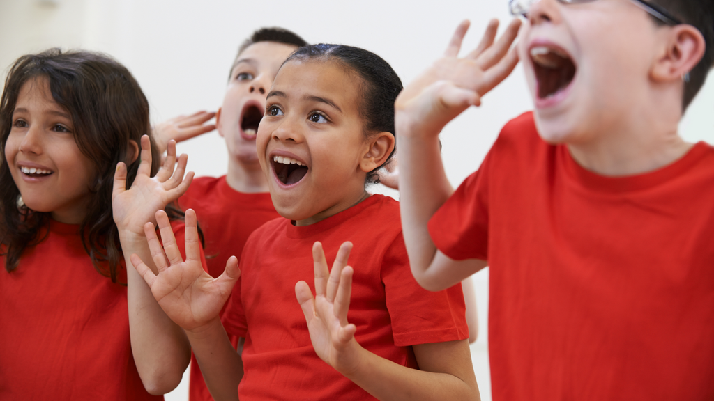 A group of young kids in red shirts act surprised in their classroom.