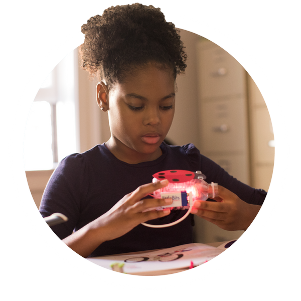 Girl holding an illuminated lady bug invention.