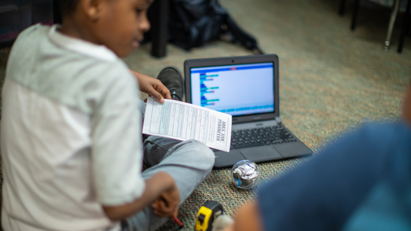 Young boy sitting on the floor with BOLT and laptop, coding robot.