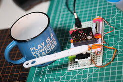 micro:bit Adapter invention with mechanical arm tapping a coffee mug.