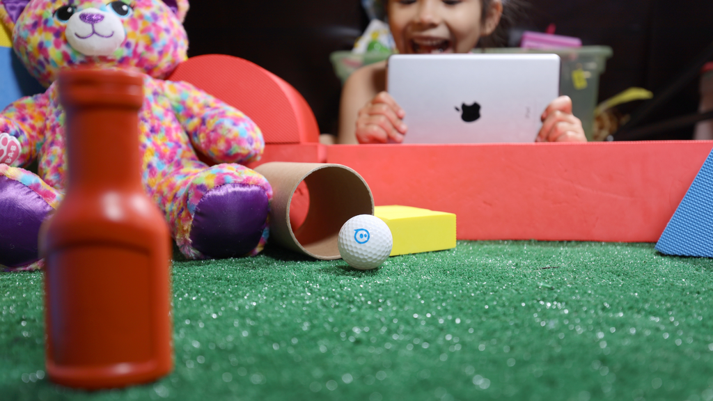 A little girl drives her Sphero Mini Golf ball on a DIY course with her iPad.