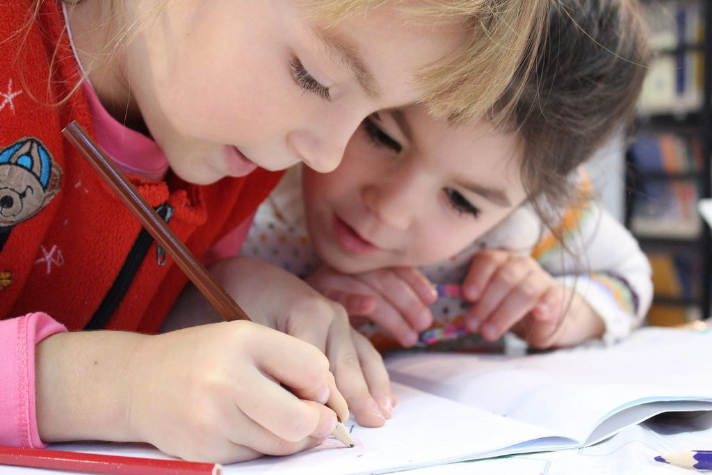 Two girls write and look on to an assignment they are working on together.