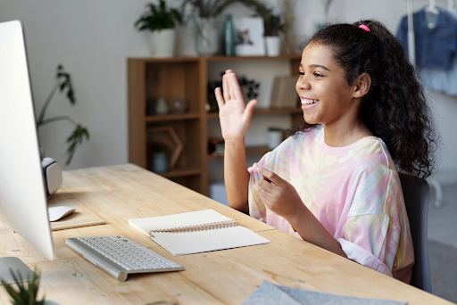 A girl sitting in front of a laptop computer at a desk raises her hand to answer a question.